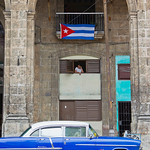 Cuban Woman, Flag and blue 1950's American car, Havana, Cuba